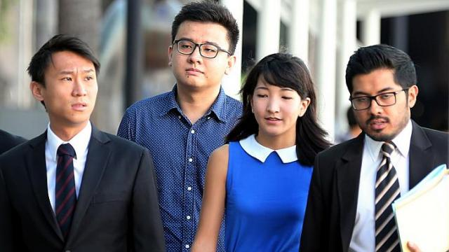 Ms Ai Takagi (blue dress) and Mr Robin Yang Kaiheng (second from left), who are behind sociopolitical website The Real Singapore, were charged with seven counts of sedition and another for failing to produce documents to a police officer on Tuesday. -- ST PHOTO: WONG KWAI CHOW
