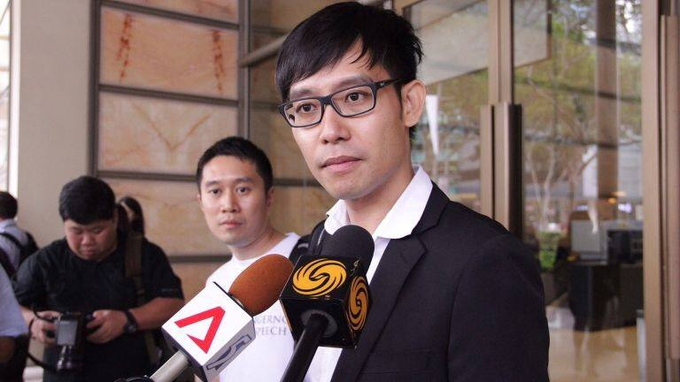 Roy Ngerng speaking to the media outside the supreme court with Jolovan Wham behind him.